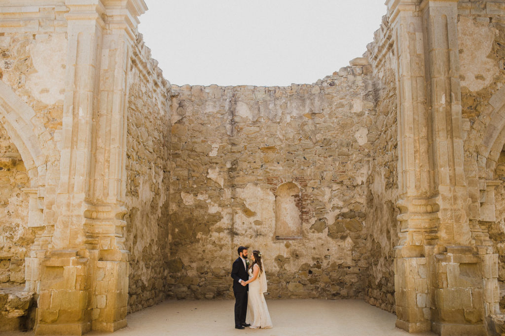 Bride and groom dancing under an arch at the mission in San Juan Capistrano CA